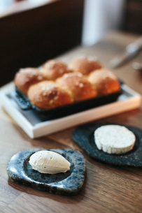 A tray of freshly baked bread rolls and cheese on a table top at a city restaurant.の写真素材 [FYI02248636]