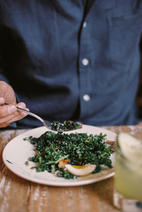 A person seated eating a meal at a table, holding a fork.の写真素材 [FYI02248651]