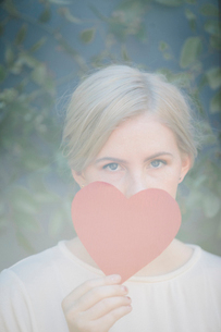 A woman holding a red heart shape in front of her face.の写真素材 [FYI02248695]