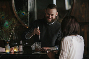 A woman and a bartender talking, and mixing drinks.の写真素材 [FYI02248699]