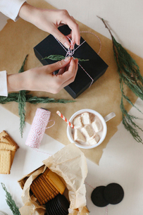 A person wrapping a parcel and a jar of homemade marshmallows.の写真素材 [FYI02248713]