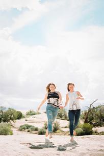 Two women running barefoot across the sand in a desert landscapeの写真素材 [FYI02248719]