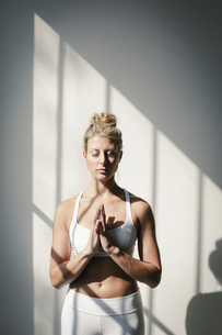 A blonde woman standing in a relaxing yoga pose by a white wall.の写真素材 [FYI02248722]
