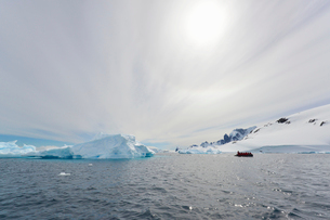View of a group of people in a rubber boat near an iceberg offshore in the Antarctic.の写真素材 [FYI02248732]