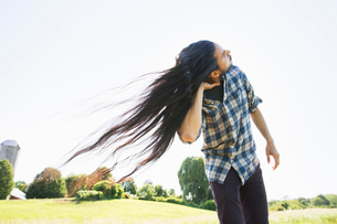 A young man shaking his head with his long hair flowing in the breeze.の写真素材 [FYI02248733]