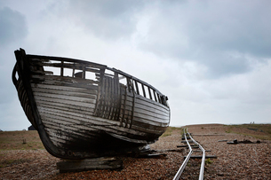 Abandoned wooden boat beached on the shingle near old narrow gauge rails.の写真素材 [FYI02248736]