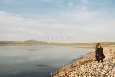 A woman collecting pebbles on the shore of a lake.の写真素材 [FYI02248754]