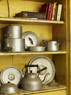 Old well worn recipe books and pots and pans on a kitchen shelf.の写真素材 [FYI02248758]