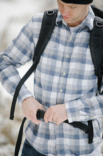 A man, a hiker fastening the belt securing his backpack.の写真素材 [FYI02248772]