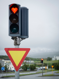 A traffic signal on the roadside, a heart shaped red light.の写真素材 [FYI02248774]