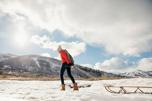A young girl in a red jacket pulling an empty sledge across the snow.の写真素材 [FYI02248786]