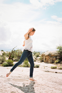 A woman wearing jeans dancing barefoot in the desert.の写真素材 [FYI02248800]