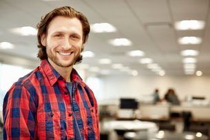 A handsome business man wearing a plaid shirt in a office.の写真素材 [FYI02248803]