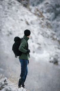 A man wearing a fleece jacket and hat, carrying a rucksack, on a mountain slope.の写真素材 [FYI02248806]