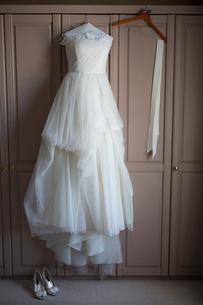 Wedding dress hanging on a wardrobe door, wedding shoes on the floor.の写真素材 [FYI02248807]