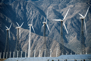 Wind power turbines in the landscape. A large number of turbine powers on a plain against a mountainの写真素材 [FYI02248833]