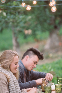 An apple orchard in Utah. Couple sitting on the ground, food and drink on a table.の写真素材 [FYI02248870]