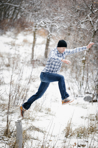 A man leaping from one post to another in the snowy woodland.の写真素材 [FYI02248874]