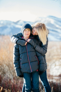 A boy in a jacket and woolly hat being hugged by his mother.の写真素材 [FYI02248878]