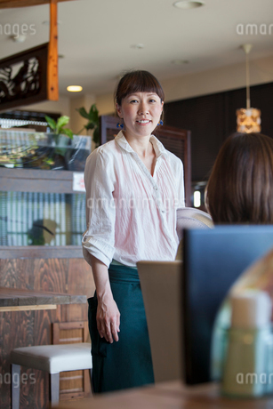 Waitress standing in a cafe, smiling.の写真素材 [FYI02248908]