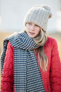 A girl in a red jacket with a large checked woollen scarf.の写真素材 [FYI02248915]