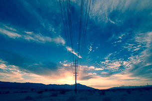 Power lines on poles reaching into the distance, in a mountain landscape.の写真素材 [FYI02248944]