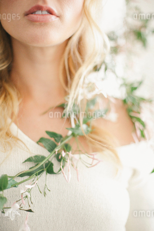 A blonde woman with a garland wound around her neck and torso.の写真素材 [FYI02248946]