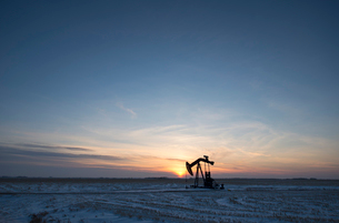 An oil drilling rig and pumpjack on a flat plain in the Canadian oil fields at sunset.の写真素材 [FYI02248966]