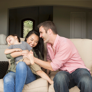 A family, a man and woman sitting side by side on a sofa  playing with their young son.の写真素材 [FYI02248993]