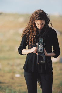 A woman taking a picture with an old fashioned medium format camera.の写真素材 [FYI02248994]