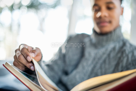 Man wearing a grey roll-neck jumper flipping through the pages of a book.の写真素材 [FYI02249024]