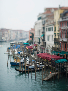 A view from above of a wide canal in Venice, with boats and traditional gondolas moored along the waの写真素材 [FYI02249044]