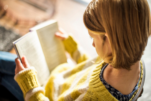 High angle view of a blond girl in a yellow jumper sitting on a chair, reading a book.の写真素材 [FYI02249045]