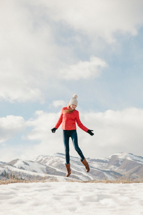 A young girl with long legs and red jacket, leaping in the air above the snowの写真素材 [FYI02249054]