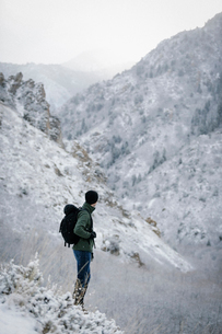 A man wearing a fleece jacket and hat, carrying a rucksack, on a mountain slope.の写真素材 [FYI02249061]