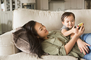Woman lying on a sofa, smiling, cuddling with her young son and looking at a cell phone.の写真素材 [FYI02249070]