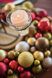 A table laid for a celebration meal. Christmas ornaments, decorations and a candle in a candle holdeの写真素材 [FYI02249078]