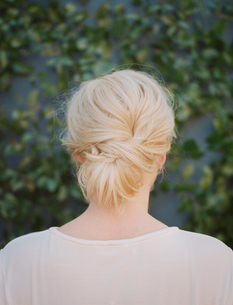 A woman with blonde hair arranged in a knot at the nape of her neck.の写真素材 [FYI02249094]