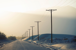 Power lines reaching into the distance, with a mountain backdrop.の写真素材 [FYI02249106]