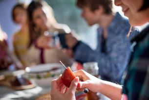 A group of people sitting at a table, eating and chatting. A woman slicing an apple.の写真素材 [FYI02249114]