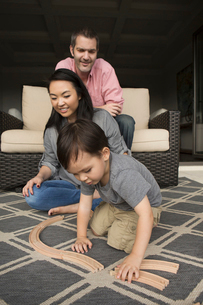 Smiling man and woman playing with their young son, building a wooden railway.の写真素材 [FYI02249146]