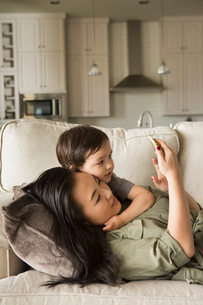 Woman lying on a sofa cuddling with her young son and looking at a cell phone.の写真素材 [FYI02249154]