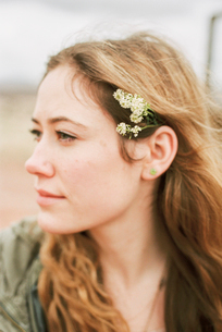 Head and shoulders portrait of a woman with a flower in her hair.の写真素材 [FYI02249165]