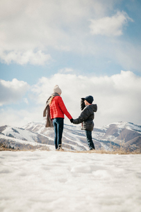 A brother and sister holding hands and looking at the snowy landscape.の写真素材 [FYI02249192]