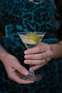 A woman holding a martini glass with a cocktail and a twist of lemon peel.の写真素材 [FYI02249206]