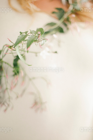 A blonde woman with a garland wound around her neck and torso.の写真素材 [FYI02249209]