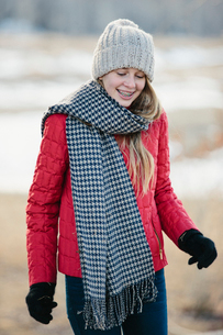 A girl in a red jacket with a large checked woollen scarf.の写真素材 [FYI02249213]
