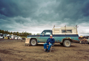 A mature man seated in a chair by his pick up truck. Piles of waste, scrap metal and wood objects.の写真素材 [FYI02249232]