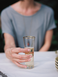 A woman holding a glass of champagne seated at a table.の写真素材 [FYI02249262]