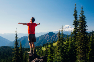 Male hiker standing with his arms outstretched on a mountain top, looking over the landscape.の写真素材 [FYI02249298]